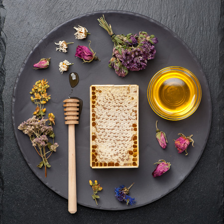 Honey and dried herbs on dark background Stock Photo