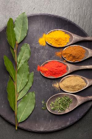Fűszerek, fűszernövények és az olívaolaj a vintage háttérben. Élelmiszer és konyha összetevők.