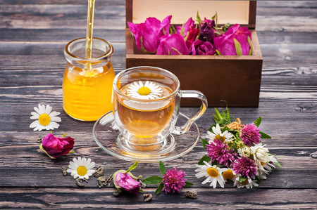 Herbal tea with honey and flowers. Chamomile tea, tea with rose petals and flowers clover. Wild herbs and flowers.