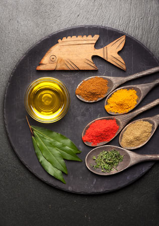 Spices, herbs and olive oil on vintage background photo