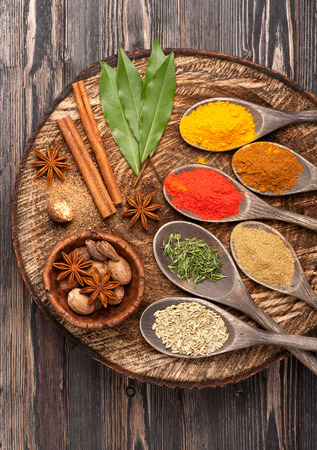 Spices and herbs on wooden board, close up