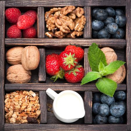 Breakfast products in vintage box: granola, nuts, berries, honey, milk