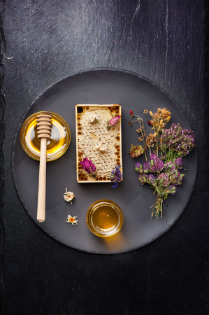 dried herbs: Honey and dried herbs on dark background Stock Photo