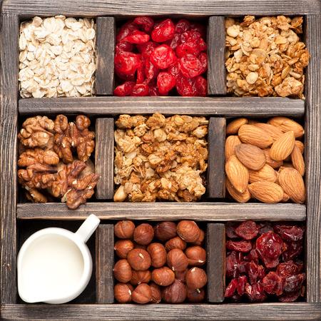 granola, zabpehely, dió, bogyók egy fadobozban. Felülnézet. Élelmiszer háttér