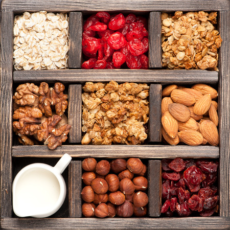 granola, oatmeal, nuts, berries in a wooden box. Top view. Food background Standard-Bild