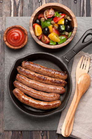 grilled sausages in a pan and vegetable salad. top view photo
