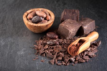 Chocolade, cacaobonen en cacaopoeder op een steen achtergrond Stockfoto