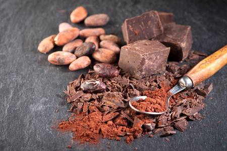 Chocolate, cocoa beans and cocoa powder on a stone background