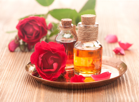 rose essential oil and rose flowers