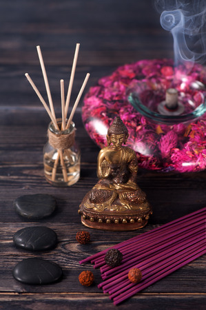 incense sticks: Spa aromatherapy meditation. Buddha statue, essential oils, incense sticks and stones massage Stock Photo