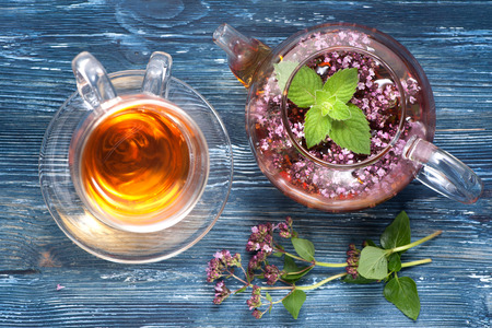 herbal medicine. Herbal tea with oregano and mint on a blue background, horizontal Imagens