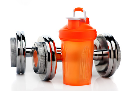 Whey protein shaker and dumbbells. Fitness and bodybuilding