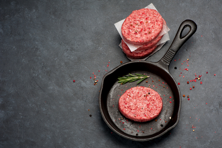 cast iron pan: Raw Ground Beef Meat Burger cutlets  in cast iron pan. Top view Stock Photo