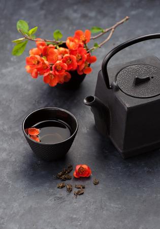 Asian cast iron tea set and flowers, black background. Tea ceremony