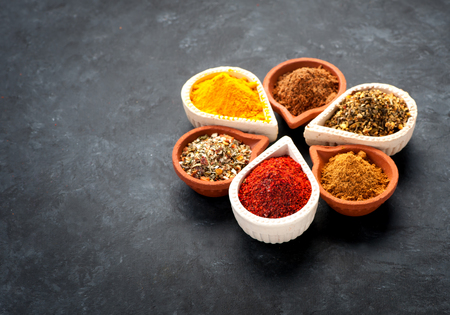 flavour: Spices, herbs and spicy spices in bowls on a black background Stock Photo