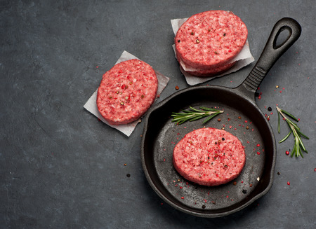 cast iron red: Raw Ground Beef Meat Burger cutlets. Top view