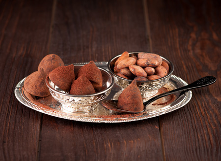 cocoa beans: Chocolate truffles and cocoa beans on wooden background