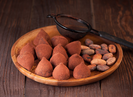 cocoa beans: Chocolate truffles and cocoa beans on the wooden table Stock Photo