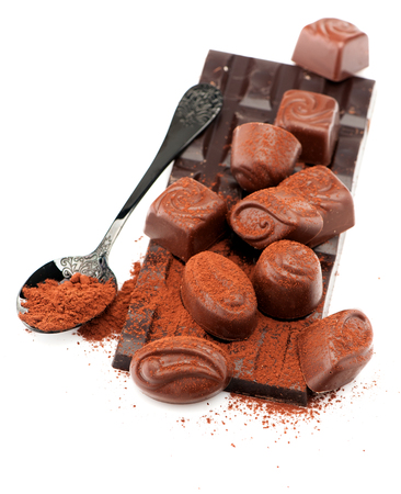 Chocolate, chocolate candy and cocoa powder on white background