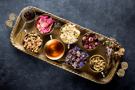 Dried medical healing herbs and herbal tea in a vintage tray