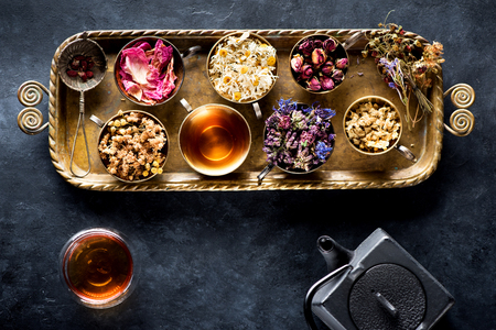 Dried herbal medicinal herbs and flowers and herbal tea in a cup and a cast iron kettle