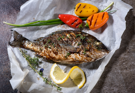 Grilled fish with vegetables, thyme and onions