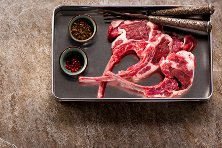 Raw meat lamb chops in a metal tray on gray concrete background