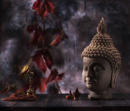 Buddha head statue, incense and sandalwood beads rosary on a background red leaves. Buddhism and meditation concept Standard-Bild