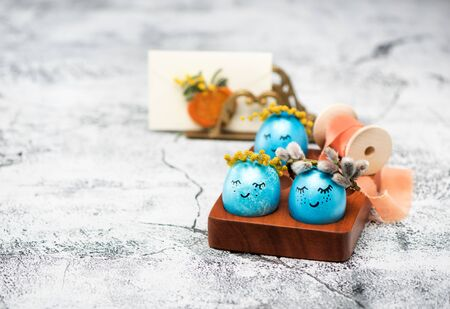 Easter blue eggs with spring flowers wreaths, greeting card and silk ribbon. Happy easter.
