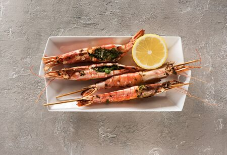 Seafood Shrimps Prawns skewers with marinade from garlic and herbs on a light concrete background, top view. Barbecue srimps prawns Banque d'images