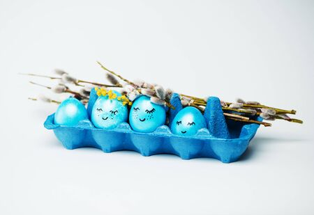 Easter blue eggs with wreaths of flowers in a carton box. Happy easter concept