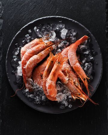 Seafood Raw Shrimps on Ice on Black Slate Background, top view