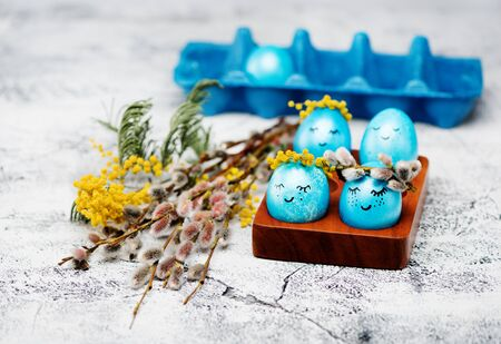 Easter blue eggs with wreaths of spring flowers on a gray concrete background, closeup. Happy easter concept