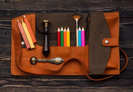 leather case with accessories for creativity. Wax seal, sealing wax, brush and pencils in leather organizer