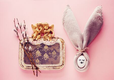 Easter bunny of eggs and napkins and vintage mirror with angels and spring flowers, flat lay. Easter greeting card Stok Fotoğraf