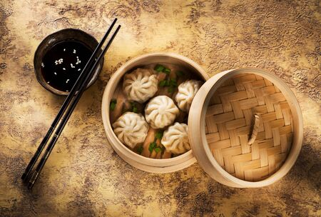 Chinese steamed dumplings in bamboo steamer with soy sauce and chopsticks, top view