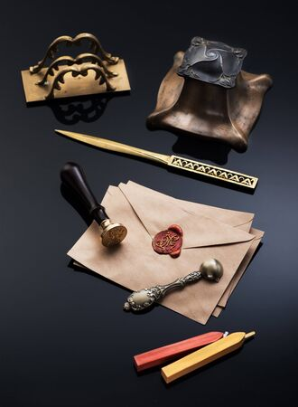 Old envelope with red wax seal and a vintage writing set: bronze inkwell, sealing wax,  letter opener and spoon for wax. writing utensils Stock Photo