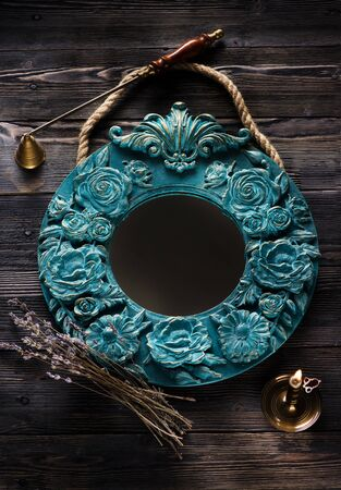 Vintage mirror with stucco molds on a wooden background, top view