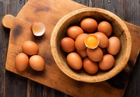 Yellow chicken eggs in a wooden bowl on a wooden texture, top view Фото со стока