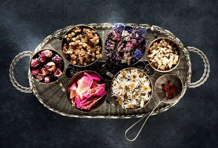 Dried medical healing herbs, flowers and herbal tea in a vintage basket