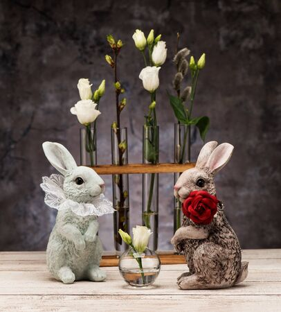 Easter bunny and spring flowers in glass vases.Easter Greeting Card