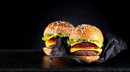 Homemade beef burger on a black background and space for text