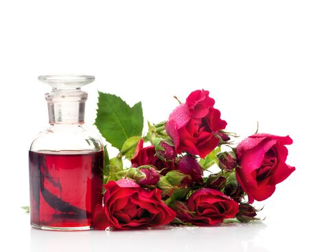 Roses massage oil in a glass bottle and flowers roses on a white background
