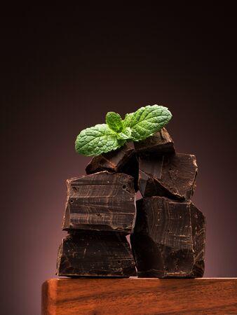 Closeup pieces dark chocolate on wooden board Stockfoto