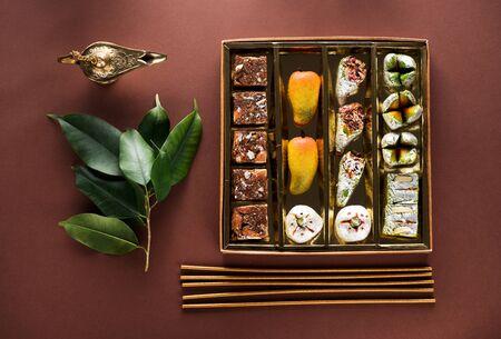 印度糖果和装在盒子里的米太,木棒和阿拉丁灯。排灯节概念,平铺,顶视图