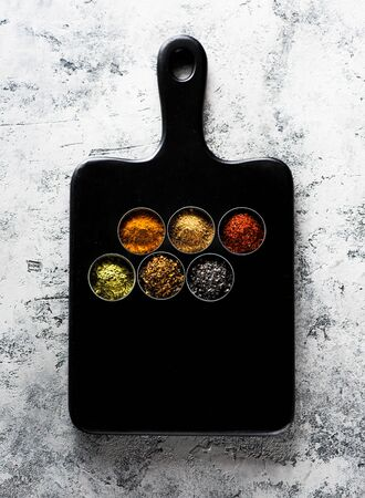 spices seasoning spicy on a wooden board, top view. Indian spices cooking on gray concrete background