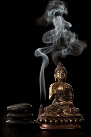 Buddha statue, incense and black stones
