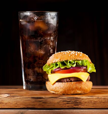 Burger cheeseburger with cutlet, cheese and vegetables and a drink with ice Imagens