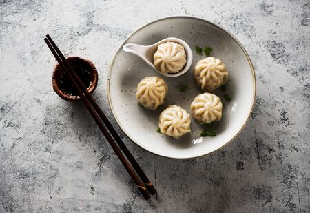 Chinese steamed dumplings in a plate with soy sauce and chopsticks on a gray concrete background top view