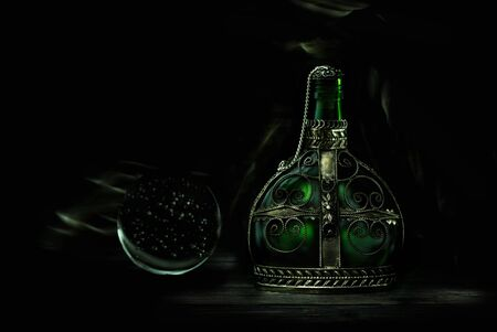 Glass green bottle with magic potion on a dark background. Magic elixir. Foto de archivo